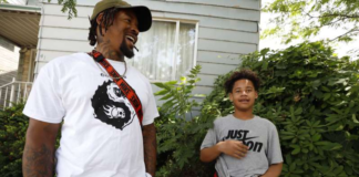 Daylan McLee and his son Avian standing in front of their home